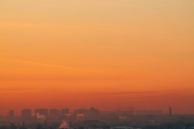 日没の民家の背後にある都市の高層ビル