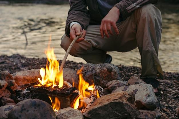 キャンプファイヤーのそばに座って雰囲気を楽しむ人。