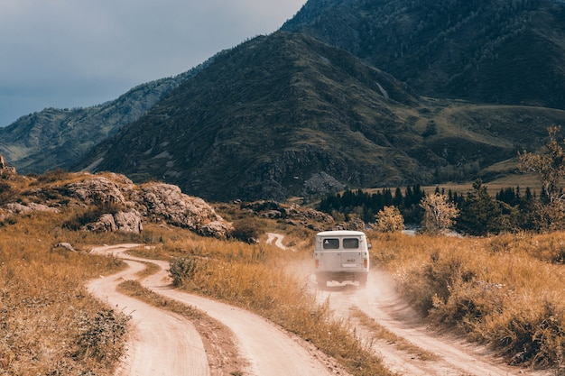 Машина движется вперед по грунтовой дороге среди гор и холмов.