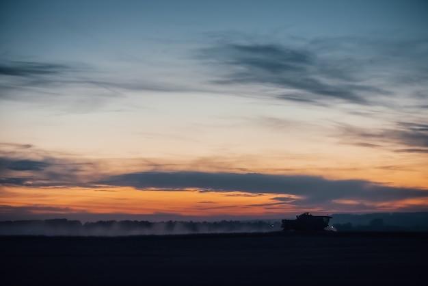 日没で小麦を収穫する収穫機のシルエット。