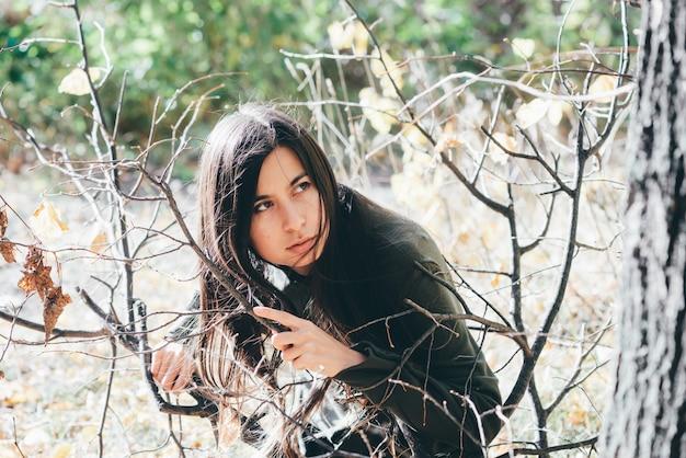 Испуганная девушка одна в лесу прячется среди желтых осенних листьев.