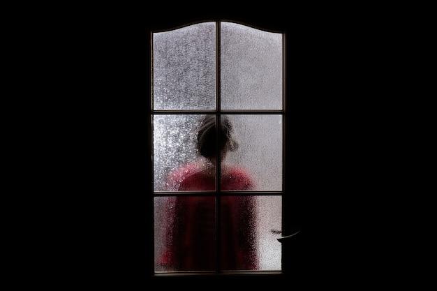 Темный силуэт девушки в красном за стеклом.