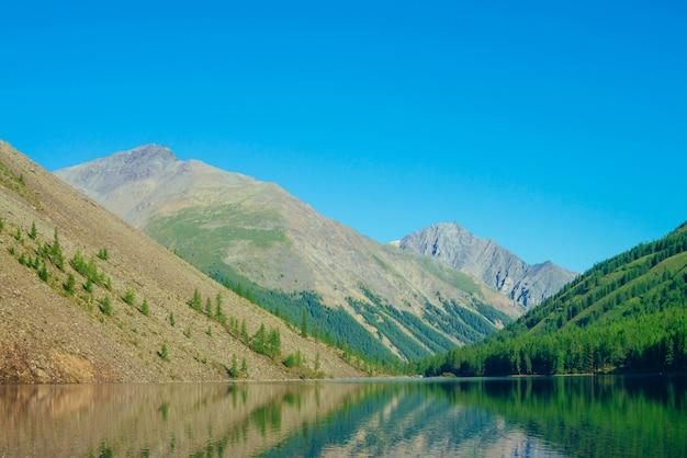 Гигантские горы отражены в чистой воде горного озера в солнечном свете.