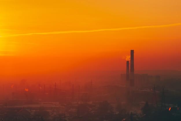 Смог среди силуэтов зданий на восходе солнца.