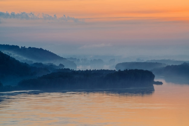 Утренняя мистическая дымка над широкой долиной реки. золотое свечение от рассвета в небе.