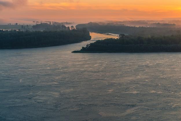 Широкая река течет вдоль берега с лесом под туманом.