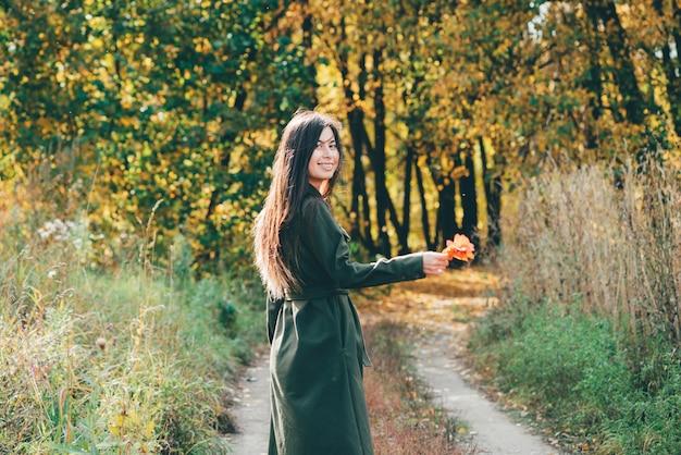Мечтательная красивая девушка с длинными естественными черными волосами в солнечном свете на фоне с разноцветными листьями.