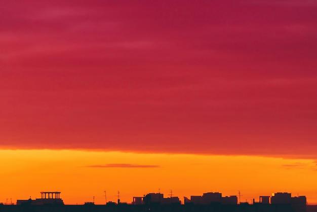 鮮やかなシュールな夜明けの街並み。都市の建物の暗いシルエットの上の驚くほど暖かい劇的な曇り空。