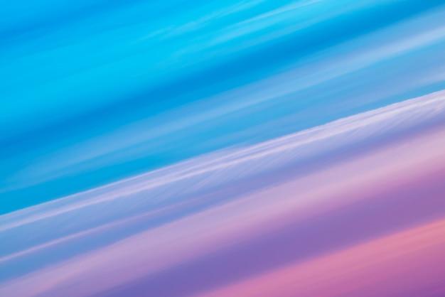 青、シアン、コバルト、ピンク、紫、マゼンタの色合いの色とりどりの縞模様のシュールな空。
