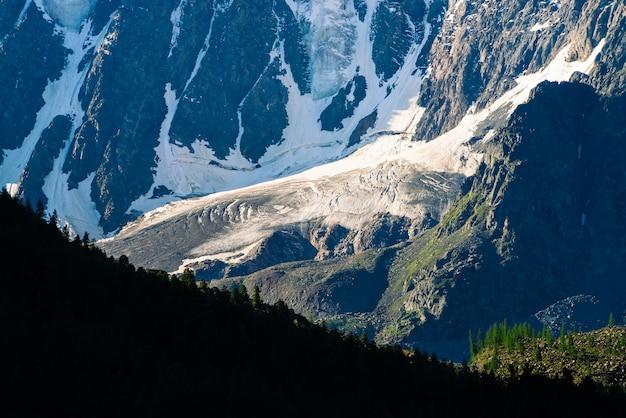 森の上の驚くべき巨大な氷河がクローズアップ。山腹で雪が降る。