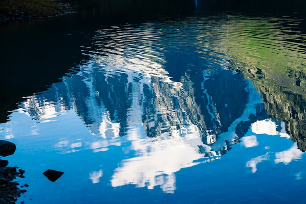 素晴らしい氷河は、山の湖のきれいな光沢のある水に反映されます。