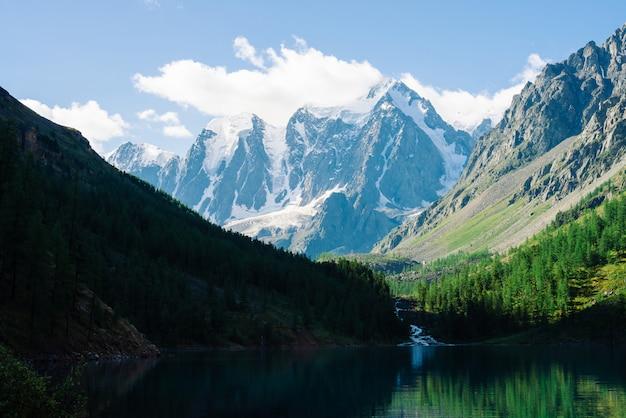 青空の下で素晴らしい氷河。森は山の湖のきれいな水に反映されます。
