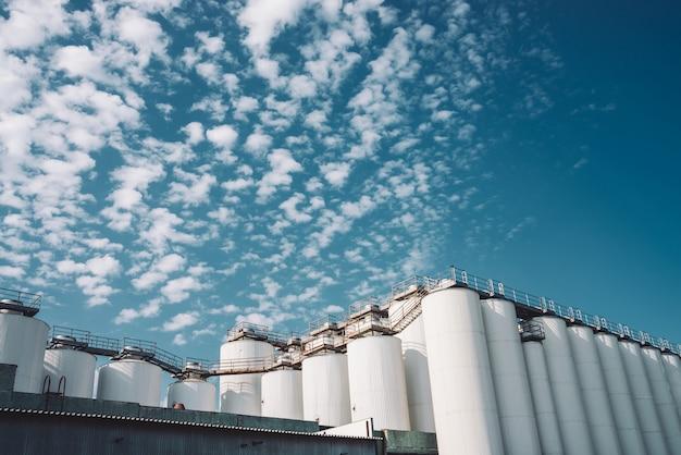 農業サイロ。穀物、小麦、トウモロコシ、大豆、ひまわりの貯蔵と乾燥。工業ビルの外観。大きな金属銀の容器のクローズアップ。