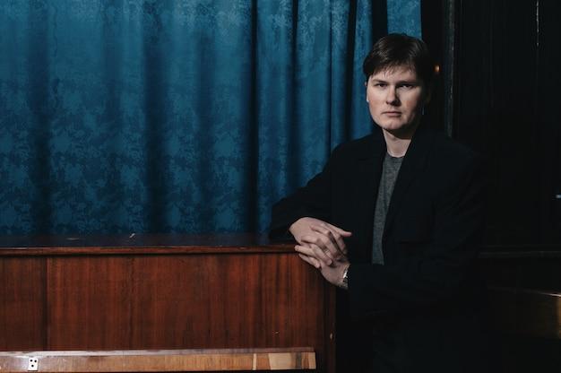 Классический музыкант-исполнитель у фортепиано. музыкальный артист в темной комнате дома культуры. портрет творческого человека в низком ключе. композитор возле музыкального инструмента.