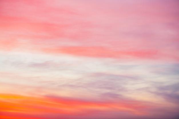 ピンクオレンジの光雲と夕焼け空。カラフルな滑らかな青空のグラデーション。日の出の自然な背景。朝の素晴らしい天国。少し曇りの夜の雰囲気。夜明けの素晴らしい天気。