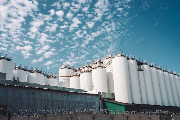 農業サイロ。穀物、小麦、トウモロコシ、大豆、ひまわりの貯蔵と乾燥。工業ビルの外観。大きな金属銀容器のクローズアップ。コピースペースを持つ農業用タンクの背景。