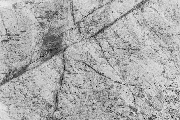 Старинный монохромный фон. грубая окрашенная стена черного и белого цвета. несовершенная плоскость оттенков серого. неровный старый декоративный фон. текстура черно-белая. однотонная декоративная каменистая поверхность