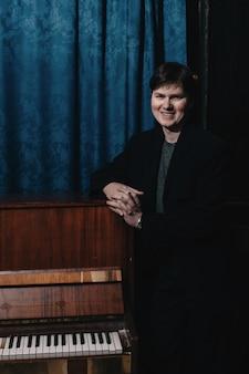 Классический музыкант-исполнитель у фортепиано. музыкальный артист в темной комнате дома культуры. портрет творческого человека в низком ключе. композитор возле музыкального инструмента. пианист на фоне фортепиано крупным планом.