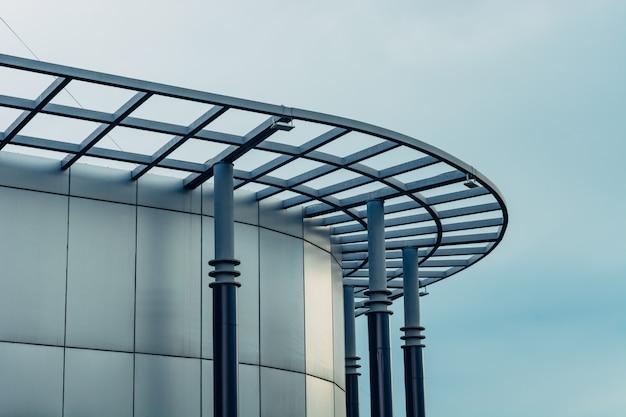 空を背景にモダンなガラス張りの建物の丸みを帯びた外観。