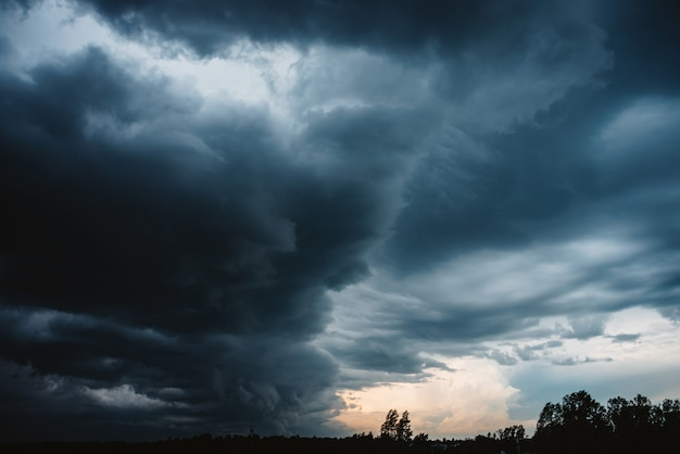 劇的なクラウドスケープ。雨の前に暗い重い雷雨の雲を通して日当たりの良い光。どんよりした雨の悪天候。ストーム警告。積乱雲の自然な青い背景。