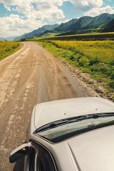 車は山岳地帯の未舗装の道路上にあります。絵のような風景。