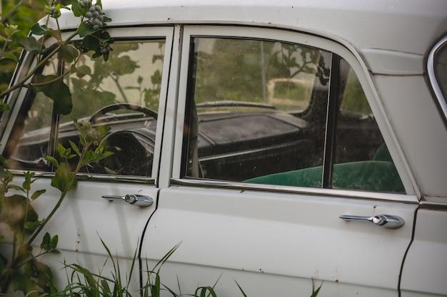 草の中の側に白いレトロ車。車のドア