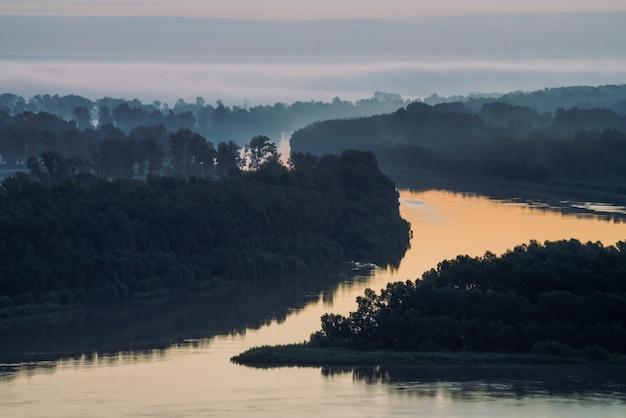 Предыдущее голубое небо отражается в речной воде. берег реки с лесом под предрассветным небом. облачное небо на фоне. туман спрятал деревья на острове.
