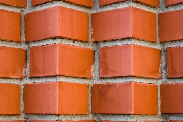 斜めに角張ったレンガのクローズアップから赤レンガの壁。