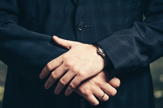 腕時計のクローズアップを持ったビジネスマンの手。