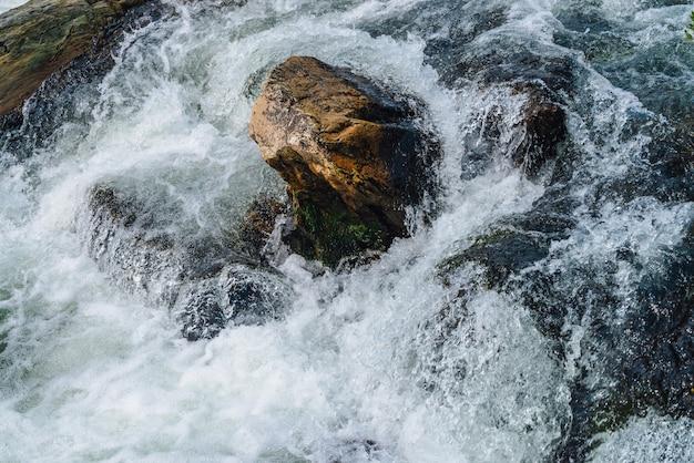 Большие валуны в горном ручье крупным планом. пороги быстрой реки с копией пространства. вспененная струя воды. быстрый поток возле мокрых камней.