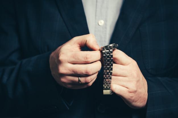 Деловой человек в костюме настраивает время в наручных часах.
