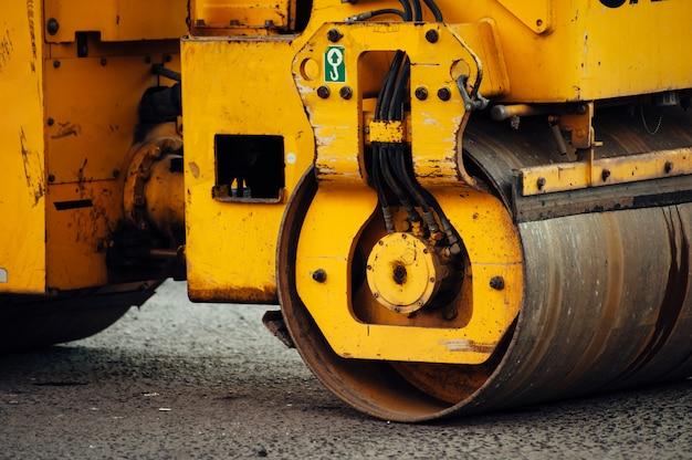 Желтый асфальт каток выравнивает дорогу. укладка нового асфальта.