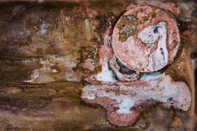 Болт ввинчивается в коррозийную медную поверхность. ржавая текстура. фон. шаблон.