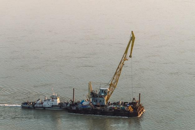 けん引船は川に沿ってクレーンでバージをけん引します。穏やかな反射水面。川の船がクローズアップ。