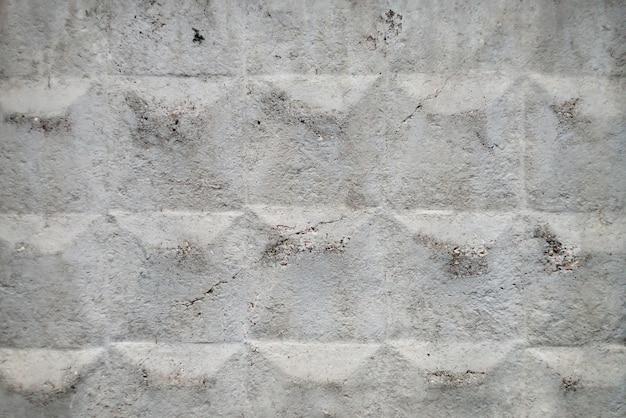 Старый советский бетонный забор с трещинами поверхности крупным планом. фоновое изображение гранж забор необычного дизайна. городская белая прочная стена.