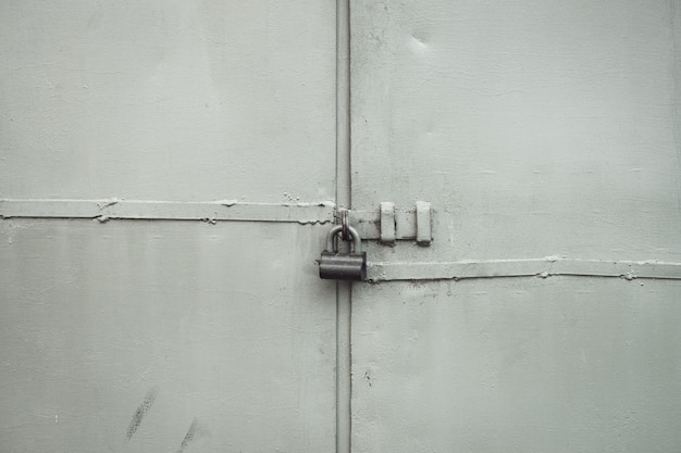 ロックのクローズアップの大まかな金属ゲート。南京錠で金属製のドアのグランジ背景。コピースペースでロックされたゲート。ロックされた入り口で汚れた工業用壁の灰色のテクスチャ。私有財産は保護されています。