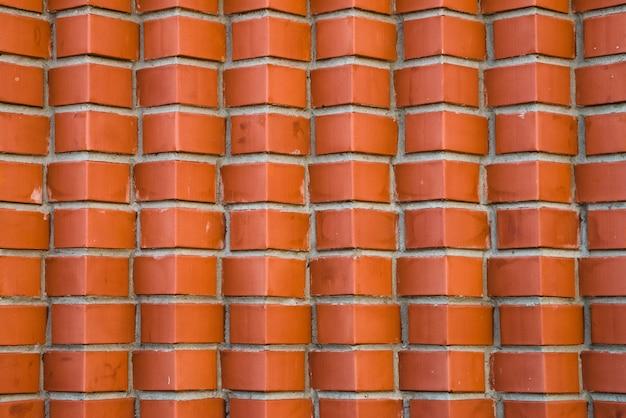 斜めに角張ったレンガの赤レンガの壁。茶色の角レンガの幾何学的な背景画像。