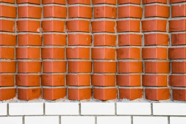 斜めに角張ったレンガの赤レンガの壁。茶色の角レンガの幾何学的な背景画像。下部に滑らかな白いレンガ造りのコンパウンド。