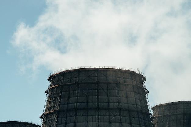 Три большие башни тэц крупным планом. белый пар от широкой трубы тэц на голубом небе. огромные трубы тэс производят пар для электроэнергии.