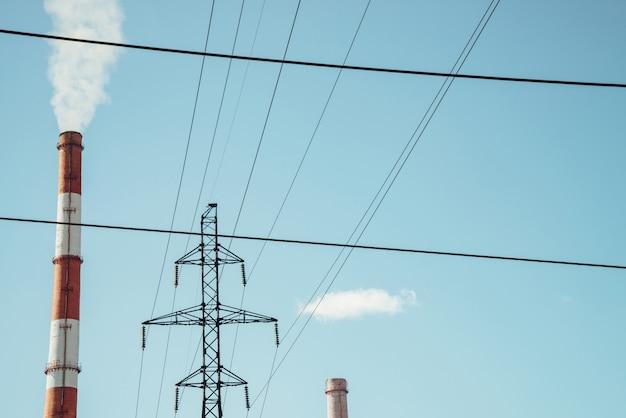 Высокая красно-белая полосатая трубка выпускает белый дым в чистое голубое небо. небольшое облако над трубой на фоне электрических полюсов и силовых проводов. конец-вверх тепловой электростанции с космосом экземпляра.