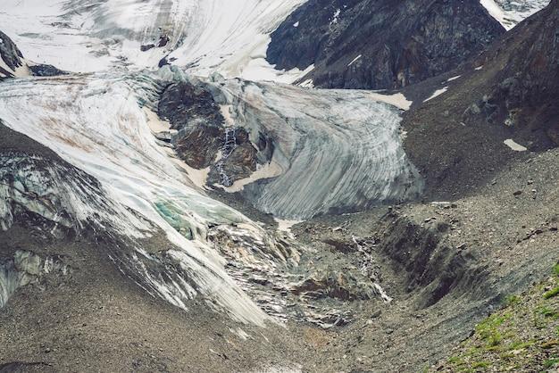 巨大な氷河のふもと。驚くほどの巨大な山の岩の自然の壁。大きな泣き目の形をした雪と氷の岩の浮き彫り。斜めの雪のライン。高地の自然の素晴らしい素晴らしいアートワーク。