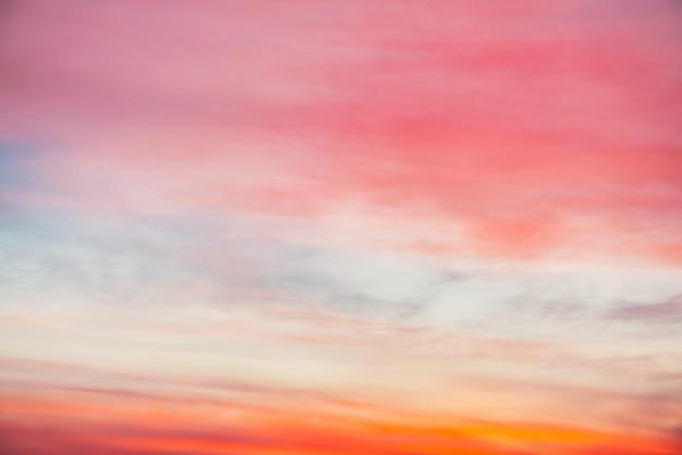 ピンクオレンジの光雲と夕焼け空。カラフルな滑らかな青空のグラデーション。日の出の自然な背景。朝の素晴らしい天国。少し曇った夜の雰囲気。夜明けの素晴らしい天気。