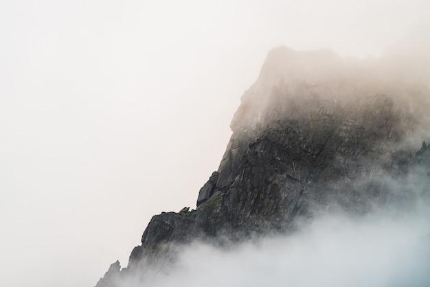 Призрачный атмосферный взгляд к большой скале в облачном небе. низкие облака среди гигантских скалистых гор. загадочное место ранним туманным утром. минималистский пейзаж с красивыми скалистыми горами. драматический мрачный туман.