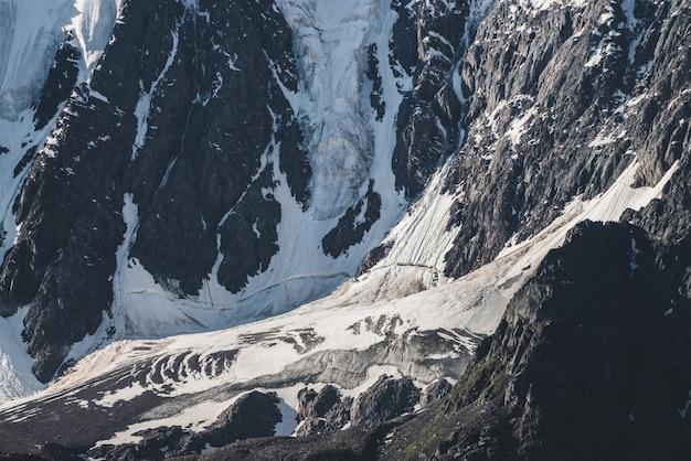 Атмосферный минималистичный текстурированный альпийский пейзаж снежной скалистой горы с языком ледника. заснеженный склон горы. трещины на льду на крутом склоне. величественные пейзажи на большой высоте.