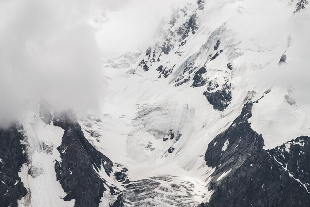 Атмосферный минималистский текстурированный альпийский пейзаж с массивным ледником на большой горе в низких облаках. заснеженный склон горы. трещины на льду. величественные туманные туманные пейзажи на большой высоте.