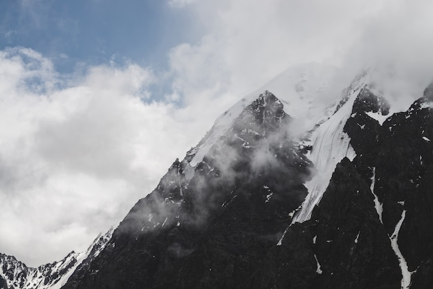 Атмосферный минималистский альпийский пейзаж с висячим ледником на снежной скалистой вершине. низкие облака среди заснеженных гор. серак на ледниковом краю. величественные туманные туманные пейзажи на большой высоте.