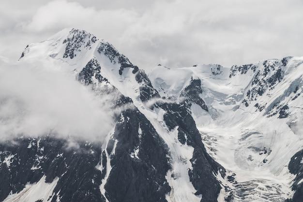 Атмосферный минималистичный альпийский пейзаж большой снежной горы с массивным ледником. низкое облако среди больших скалистых гор. язык ледника возле заснеженных горных склонов. величественные пейзажи на большой высоте