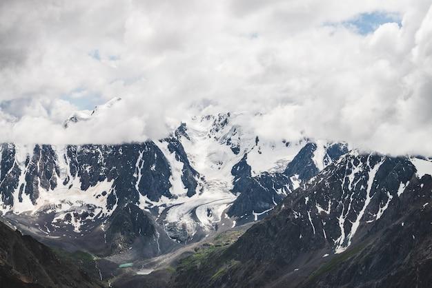 Атмосферный альпийский пейзаж с массивным свисающим ледником на гигантской горе. большой ледниковый язык на склоне горы. низкие облака среди заснеженных гор. трещины на льду. величественные пейзажи на большой высоте.
