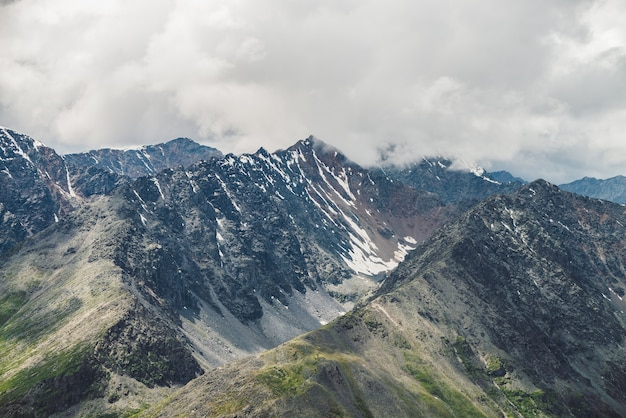 Атмосферный альпийский пейзаж с большой горный хребет и заснеженный пик в низких облаках. облачное небо над огромной горной цепью. гигантские снежные скалистые скалы и скалистая долина. величественные пейзажи на большой высоте