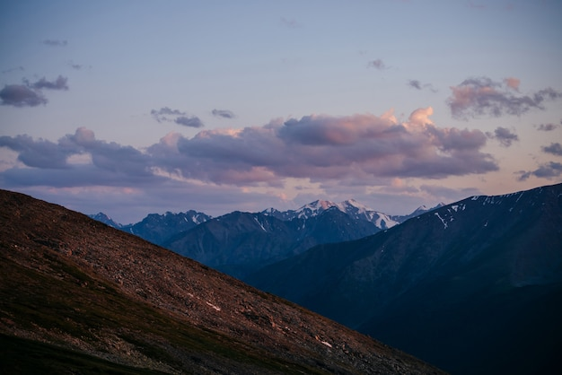夜明けの空に薄紫色の雲の下で素晴らしい山々と大気の高山の風景。マゼンタの山の素晴らしい日の出風景。夕日にピンクの雪と氷河に素晴らしい景色。紫の夕暮れの空